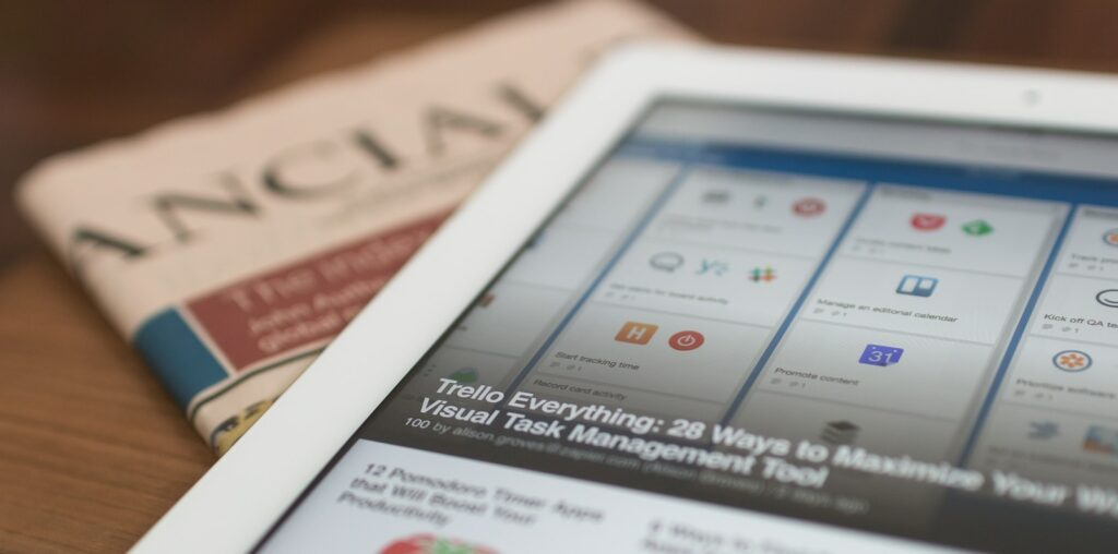 white tablet computer on top of newspaper
