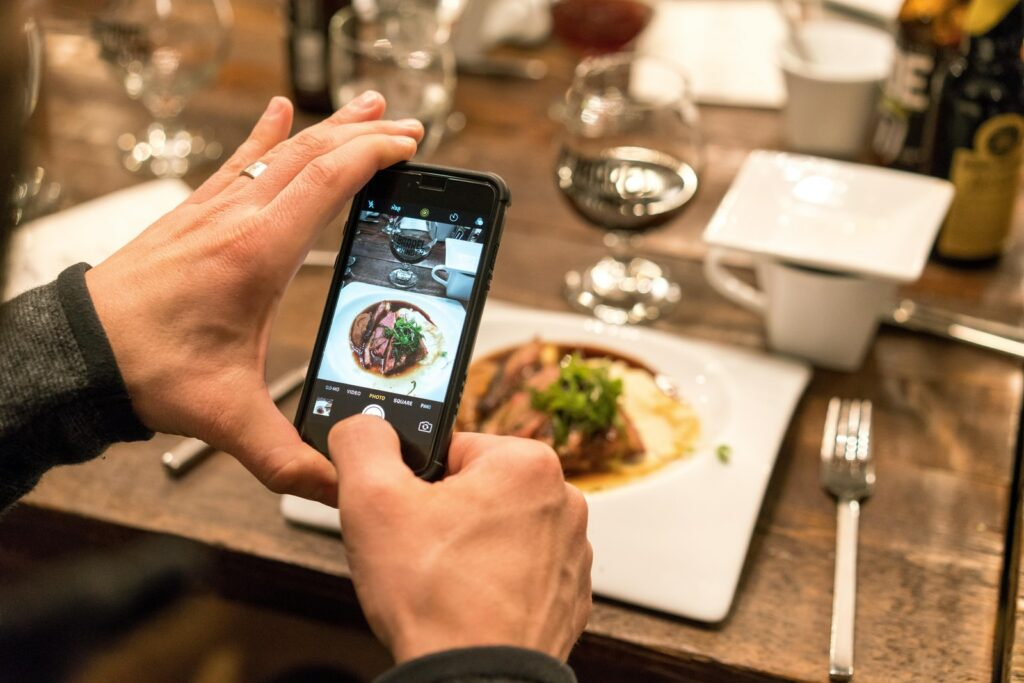 person holding black iPhone taking picture of cooked food